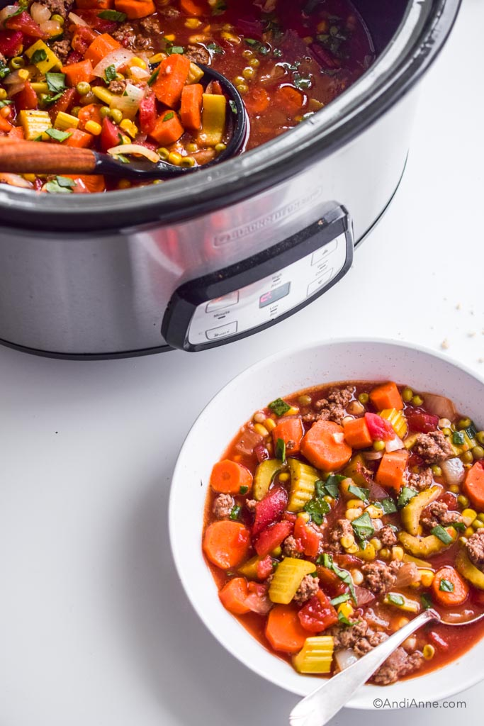 slow cooker with hamburger soup and soup spoon is above a white bowl that has hamburger soup in it as well