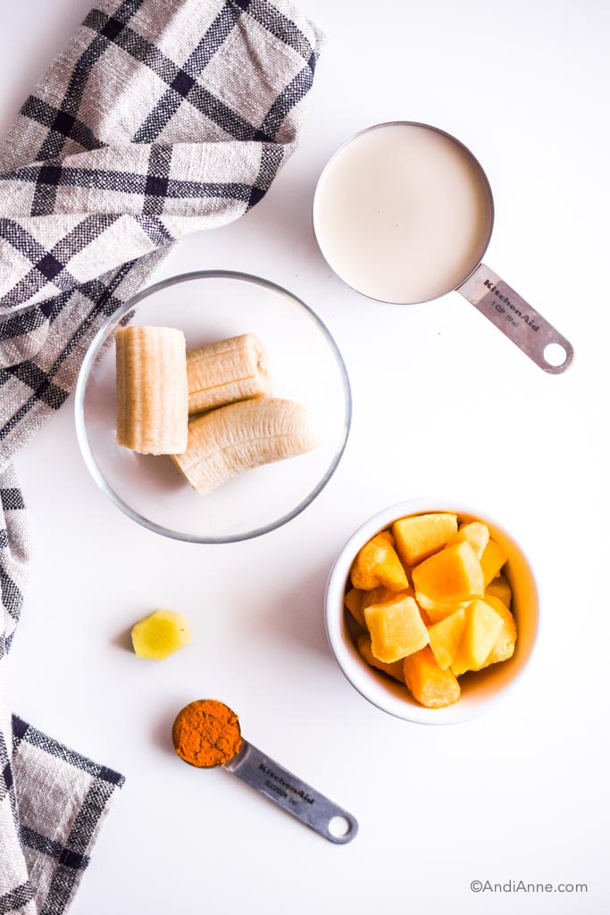 bowl of chopped frozen banana, 1 cup milk, bowl of frozen mango, piece of fresh ginger, spoon of turmeric powder on white table with striped black towel