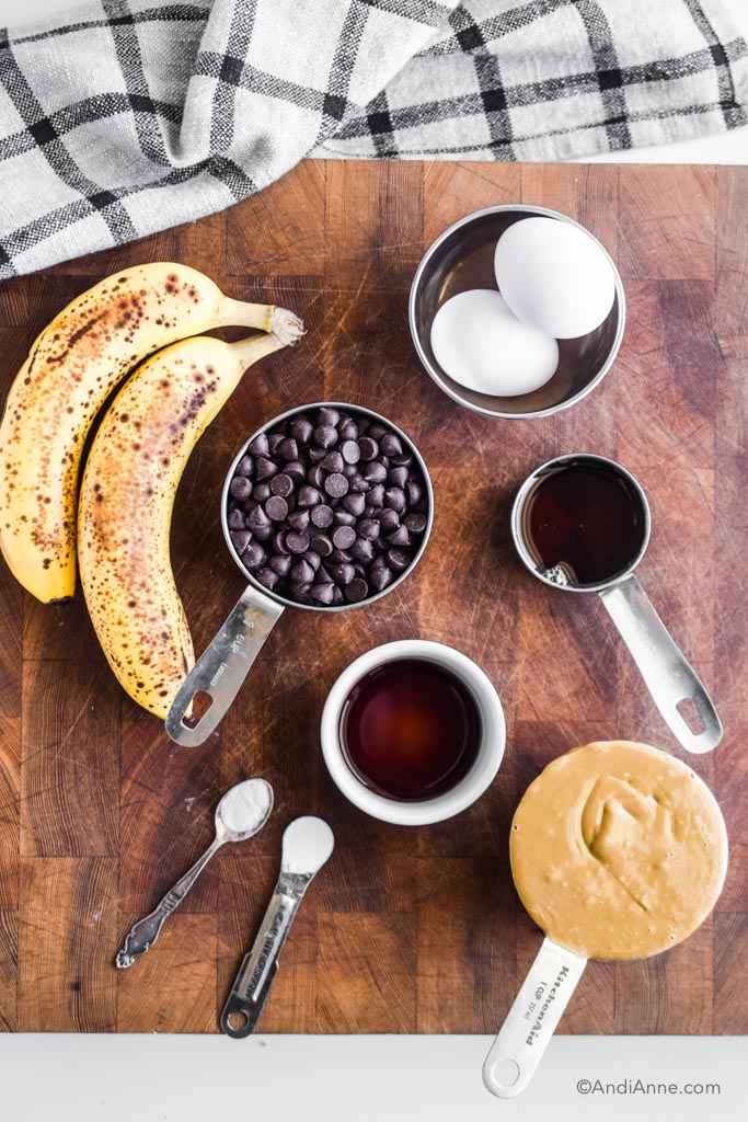 ingredients on wood cutting board. Includes ripe bananas, eggs, chocolate chips, maple syrup, vanilla, and seed butter
