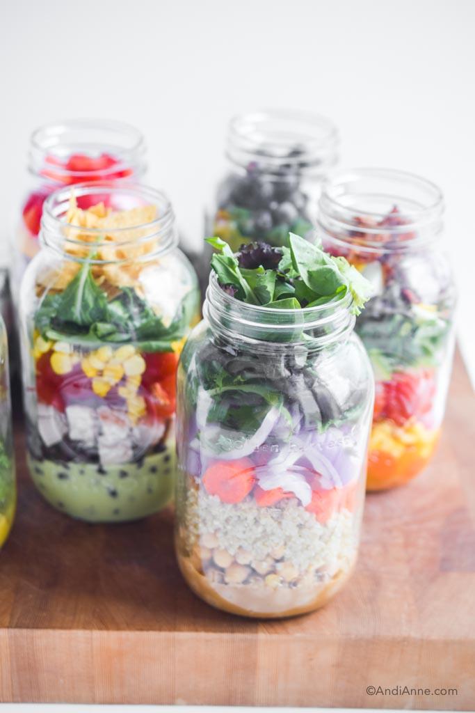 six healthy mason jar salads on a wood cutting board