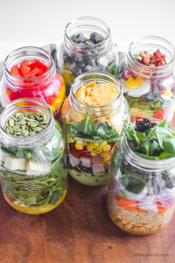 six different salads inside mason jars on a wood cutting board