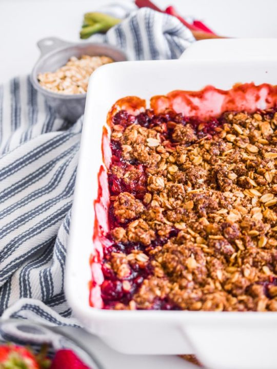 close up detail of strawberry rhubarb crisp in a white baking dish with striped kitchen towel beside it.