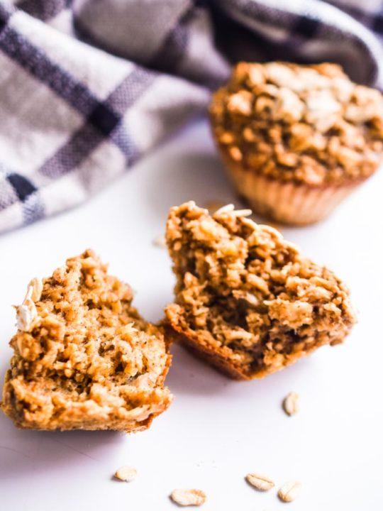 banana oatmeal muffin broken in half. A full muffin behind it.