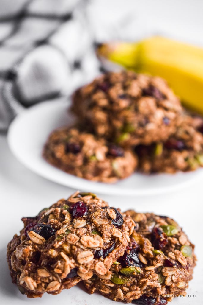 banana cranberry breakfast cookies stacked on eachother with white plate and kitchen towel in background