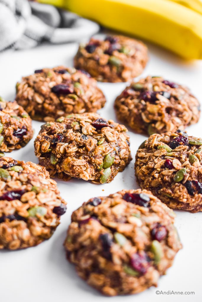 banana cranberry breakfast cookies on white table with bananas in the background