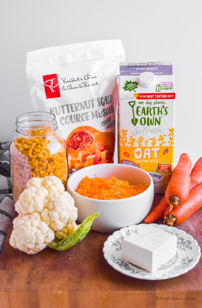 ingredients piled together to make mac and cheese. A bag of frozen squash, carton of milk, jar of pasta noodles, cauliflower, bowl of shredded cheese, carrots and cube of cream cheese