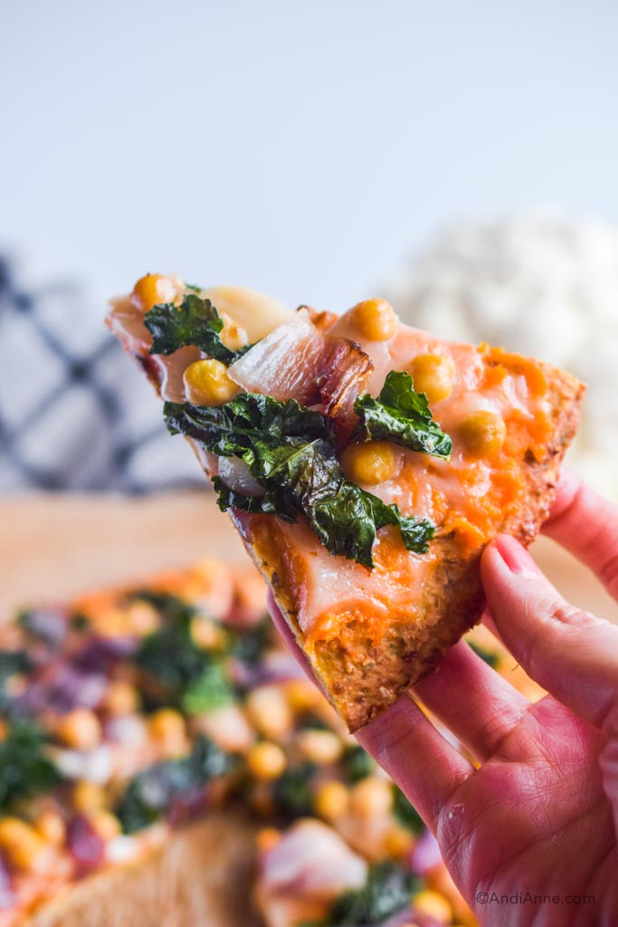hand holding up a slice of kale chickpea cauliflower pizza with whole pizza in background