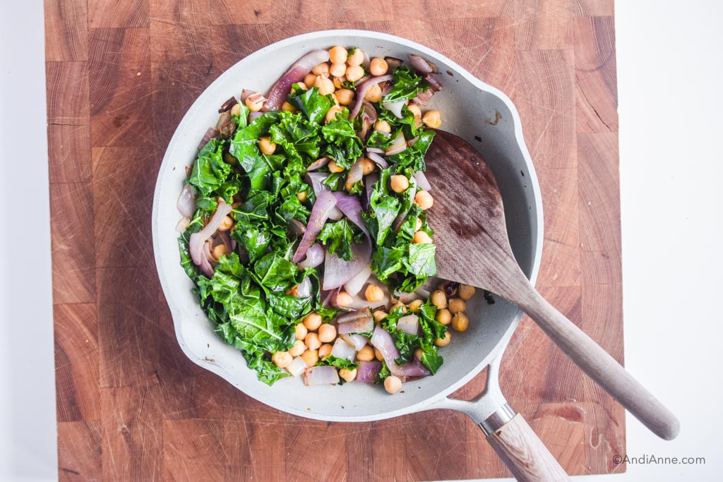 sauteed kale, chickpeas, and onions in a frying pan with a wooden spatula. Pan is sitting on a butcher block cutting board.