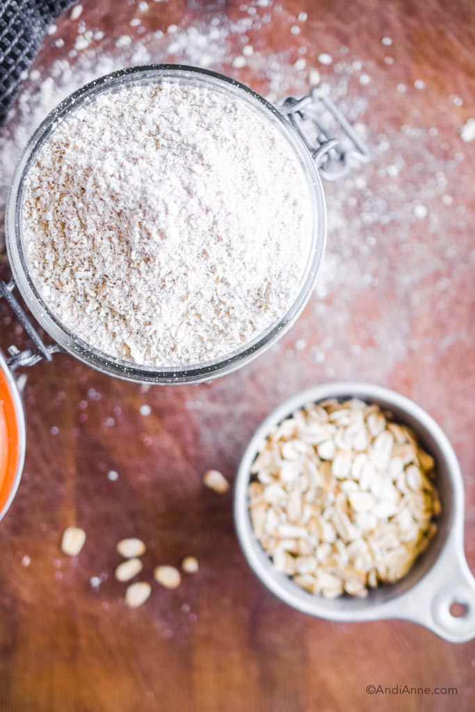 homemade oat flour in a jar with rolled oats in a small cup