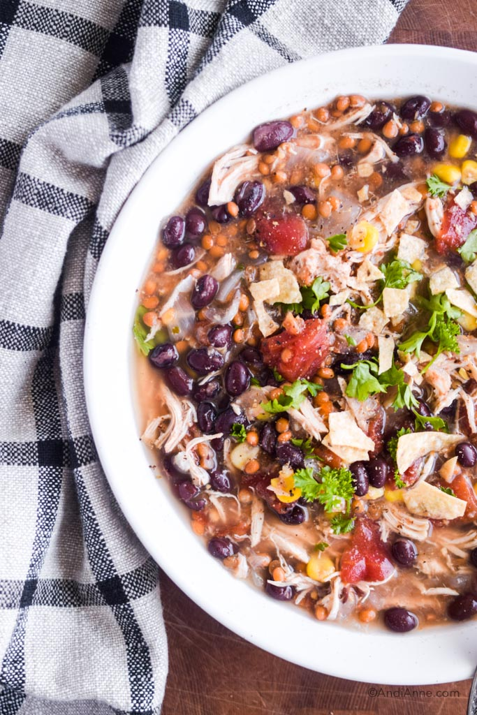 Close up of chicken lentil taco soup in a white bowl with black and white plaid kitchen towel beside the bowl