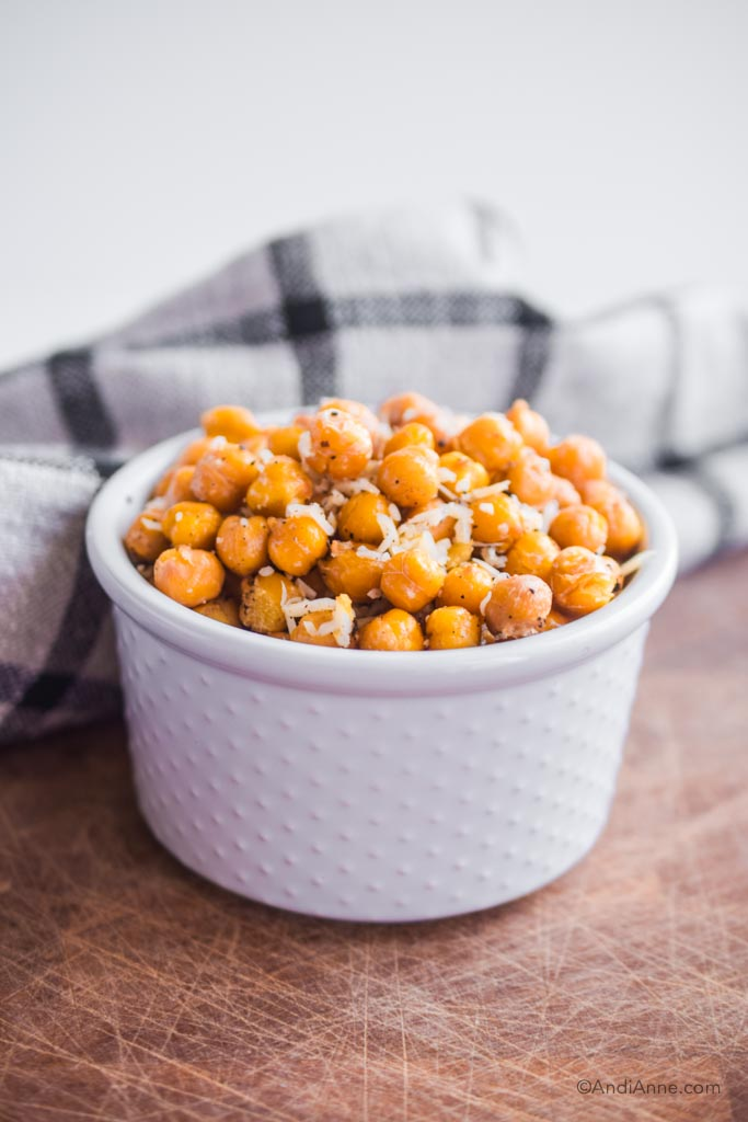 roasted parmesan chickpeas piled in a white bowl with a kitchen towel in the background