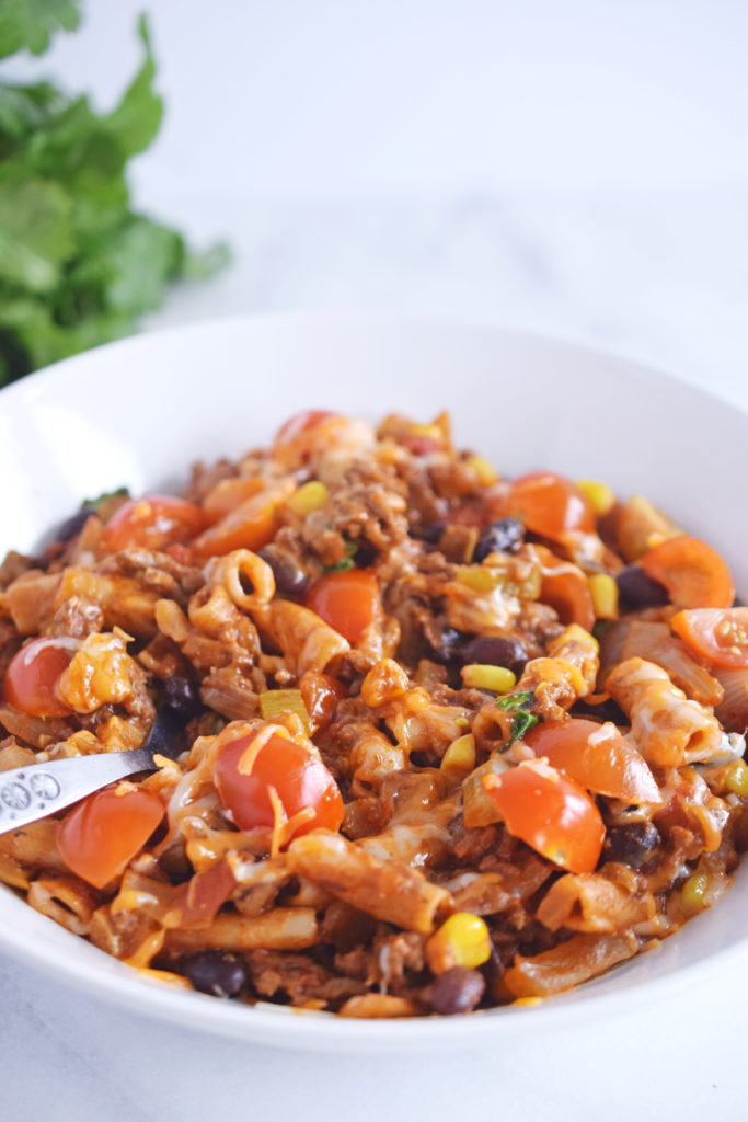 one pot taco pasta recipe in white bowl with spoon