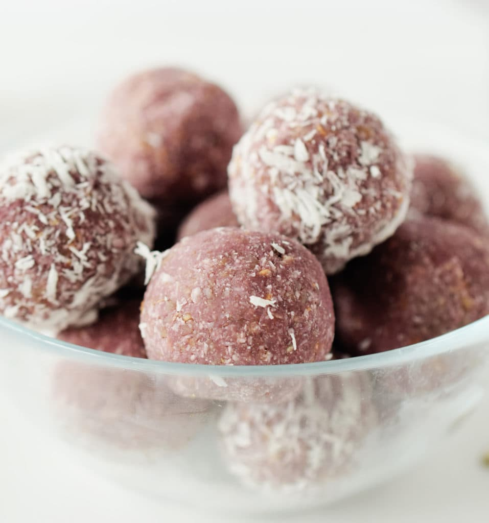 A glass bowl of with the energy balls stacked inside