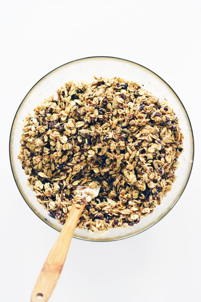 glass bowl holding mixture of superfood granola with small spatula