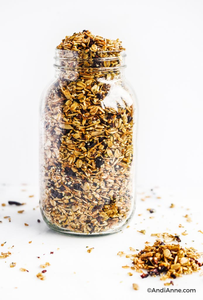 homemade superfood granola poured into a large glass jar and sprinkled on the white counter surrounding jar
