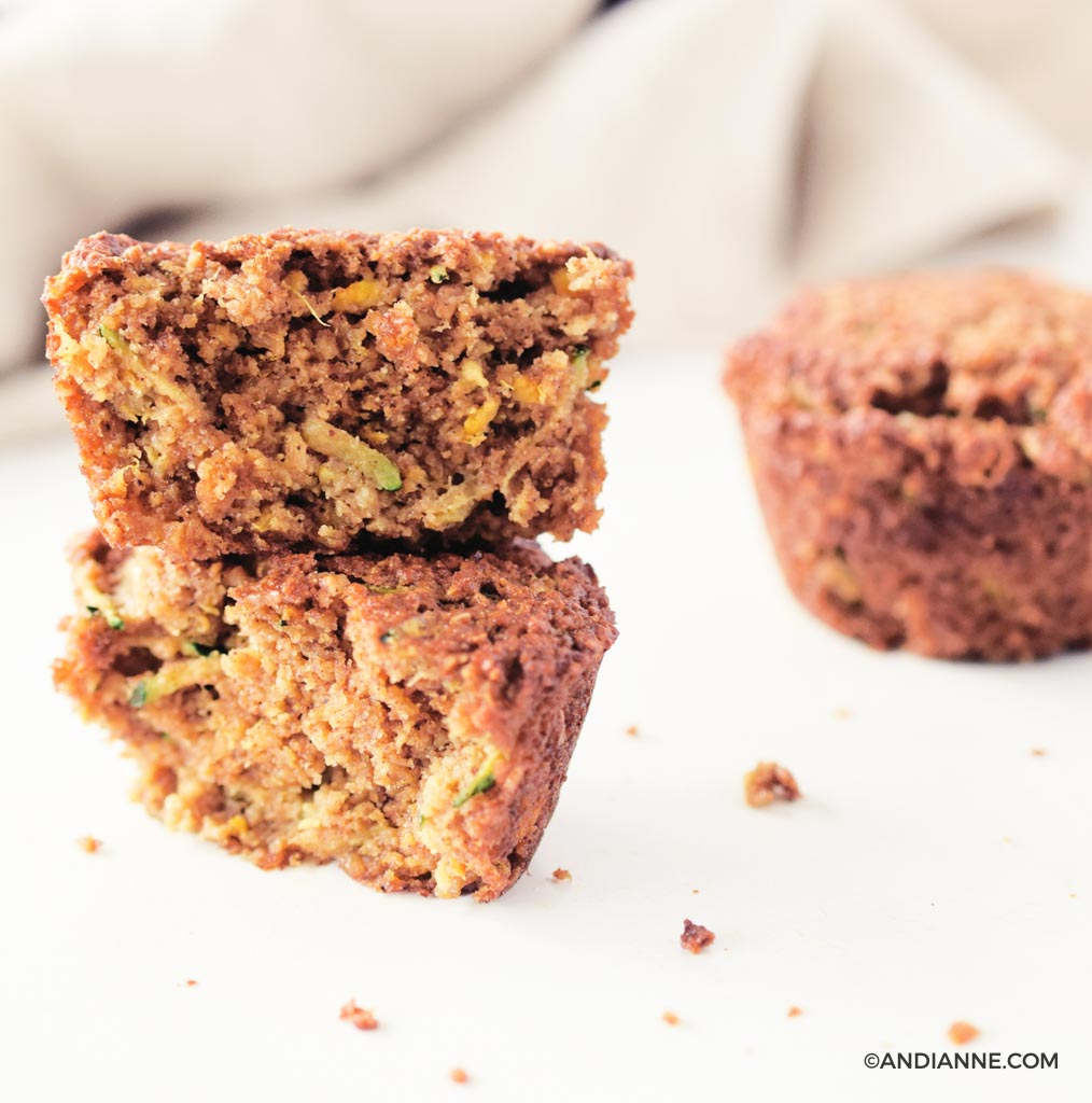 zucchini orange oat muffins stacked on top of eachother. Beige napkin in background.