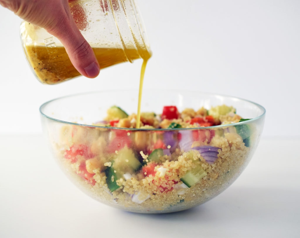 honey dijon quinoa salad in glass bowl with salad dressing being poured over top out of a mason jar
