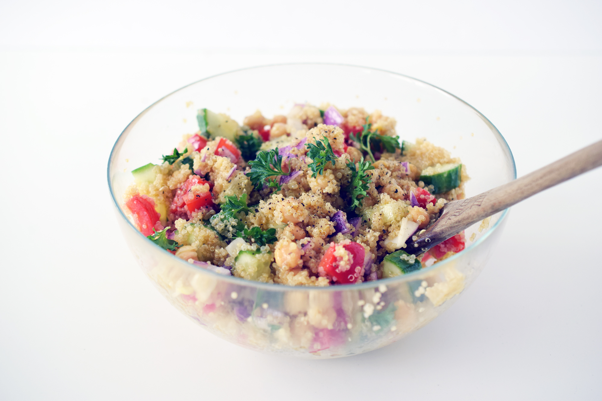 honey dijon quinoa salad in glass bowl with wooden spoon