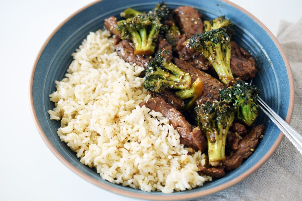 beef and broccoli stir fry with rice in blue bowl