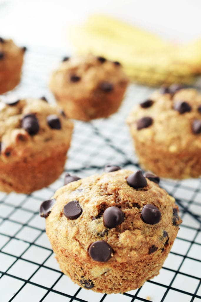 spelt muffin with banana and chocolate chips on a black cooling  rack. bananas blurred in background.
