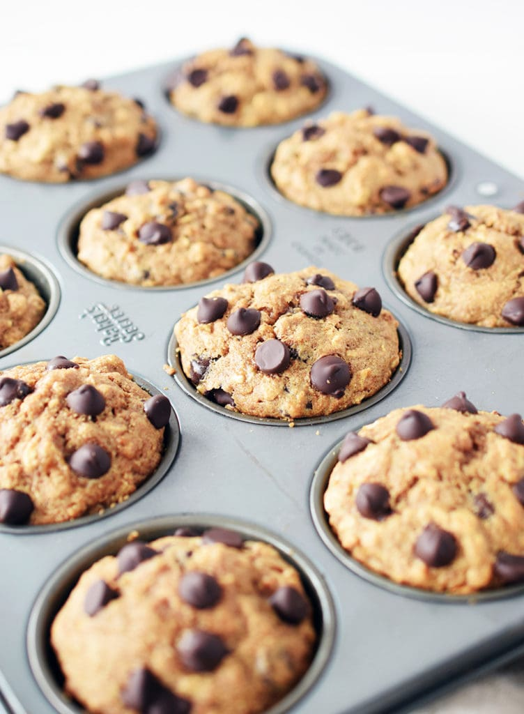 angled view of spelt muffins in muffin pan. Close up detail of chocolate chips on top