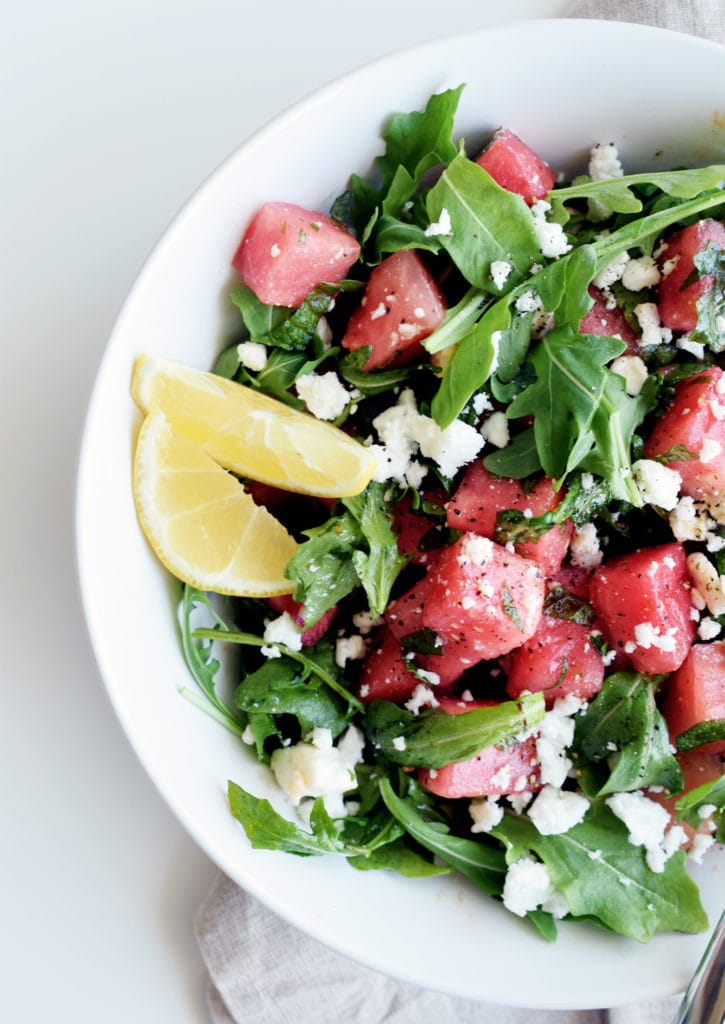 watermelon arugula salad with lemons in a white bowl