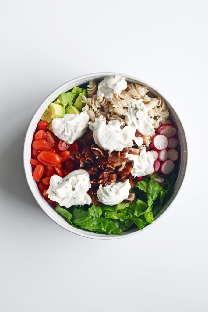 ingredients in a white bowl with dressing dolloped on top