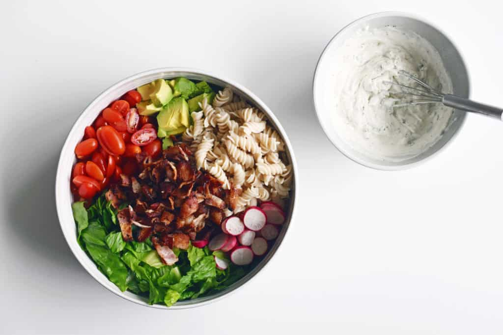 Tomatoes, bacon, pasta noodles, radish and lettuce in a large bowl, with premixed salad dressing in a smaller bowl with whisk