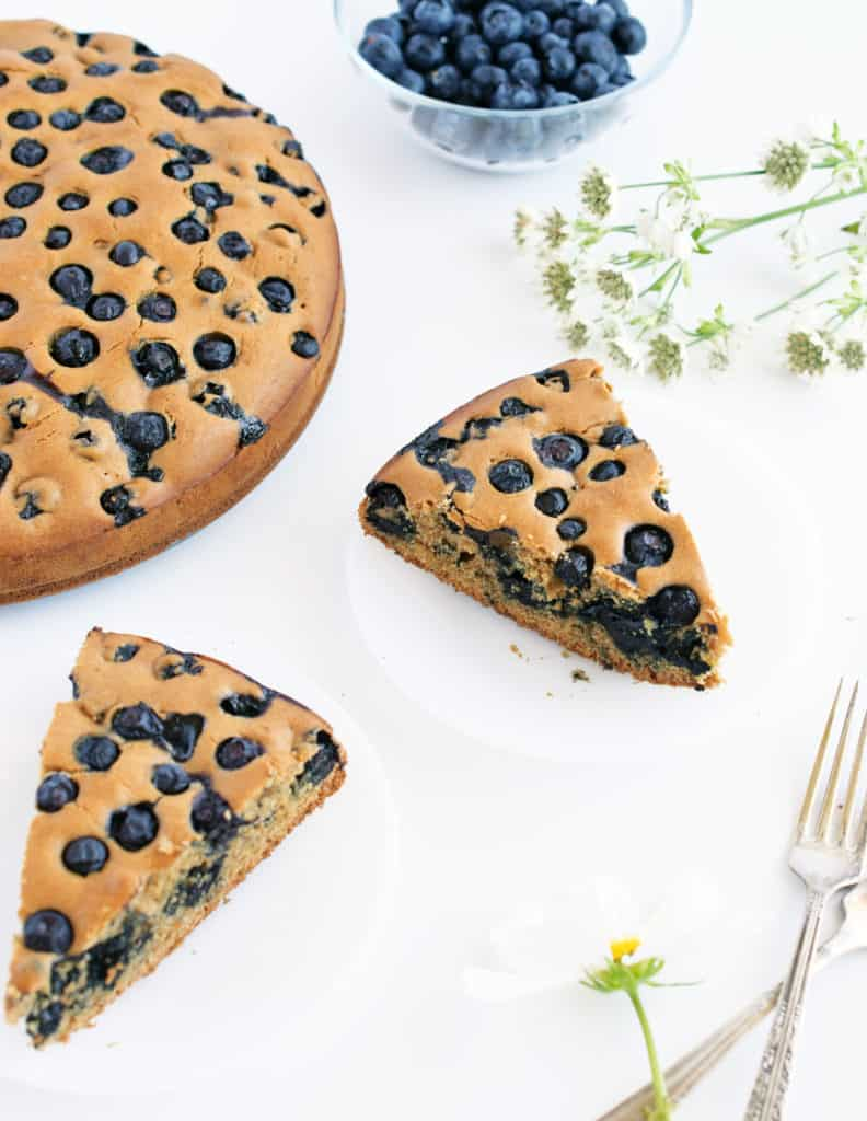 Slices of gluten free blueberry cake on plates with serving forks