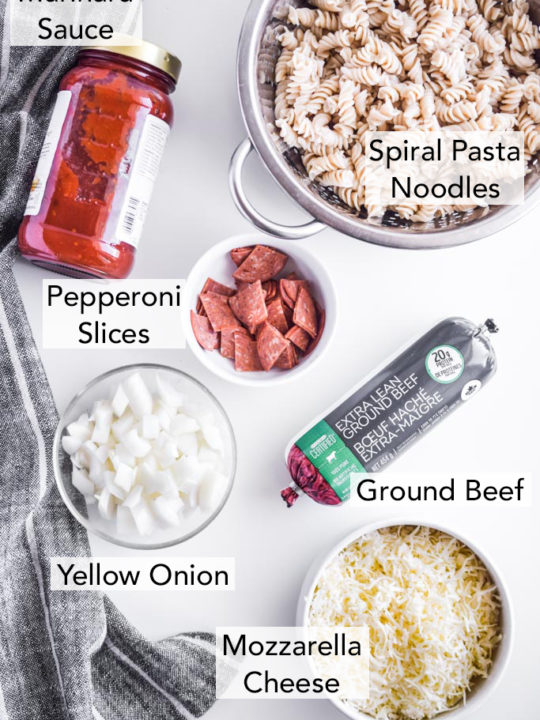 ingredients for the recipe in separate containers on a white table, including pepperoni slices in a white bowl, spiral pasta noodles, marinara, uncooked ground beef in a tube, chopped onion, and sliced mozzarella cheese