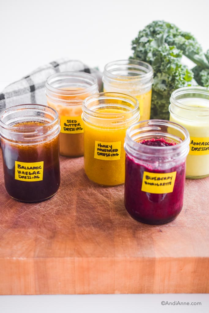 six different healthy salad dressings in 8 oz mason jars. Each one has a yellow label with name written on front.