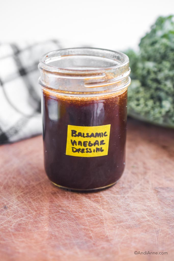 balsamic vinegar dressing in a mason jar with yellow label on front.