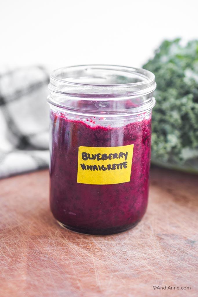 blueberry vinaigrette in a mason jar on wood cutting board.