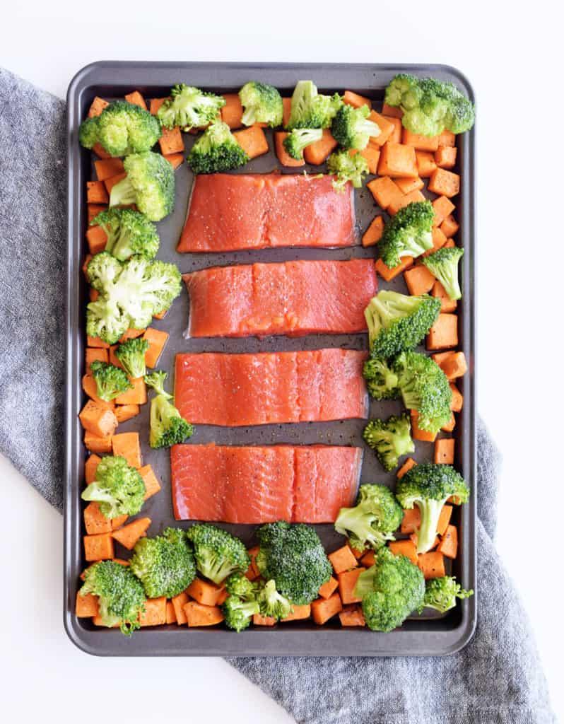 raw teriyaki salmon on a baking sheet surrounded by raw broccoli and chopped sweet potato