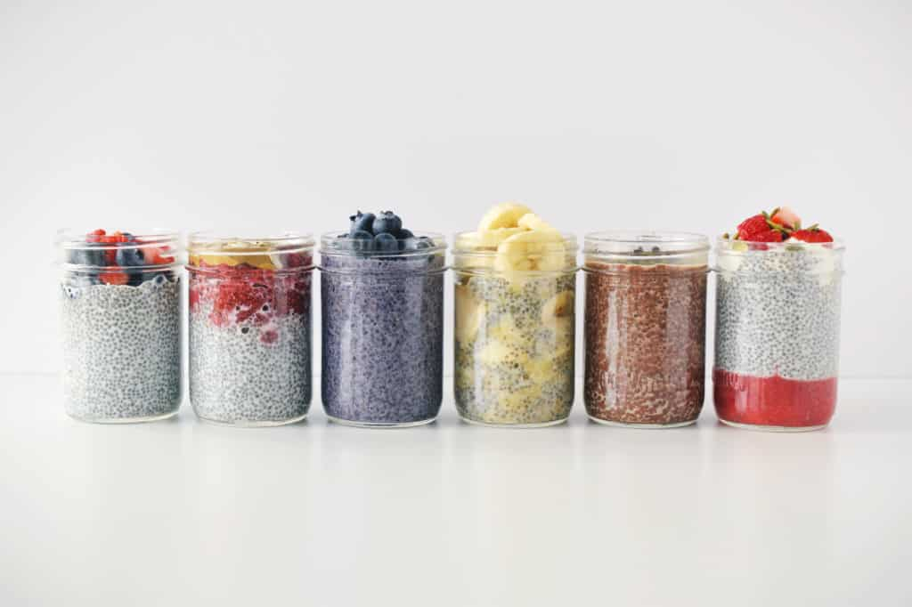 six chia pudding recipes in mason jars on white background side by side