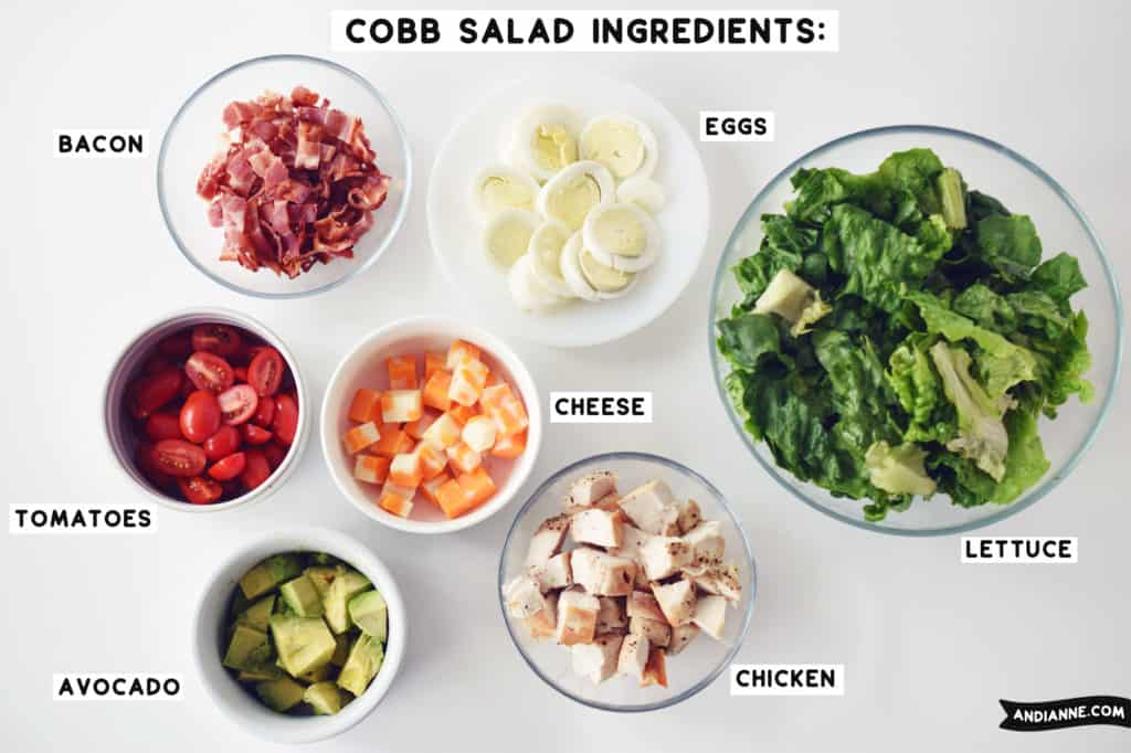 cobb salad ingredients in separate glass and white bowls beside eachother