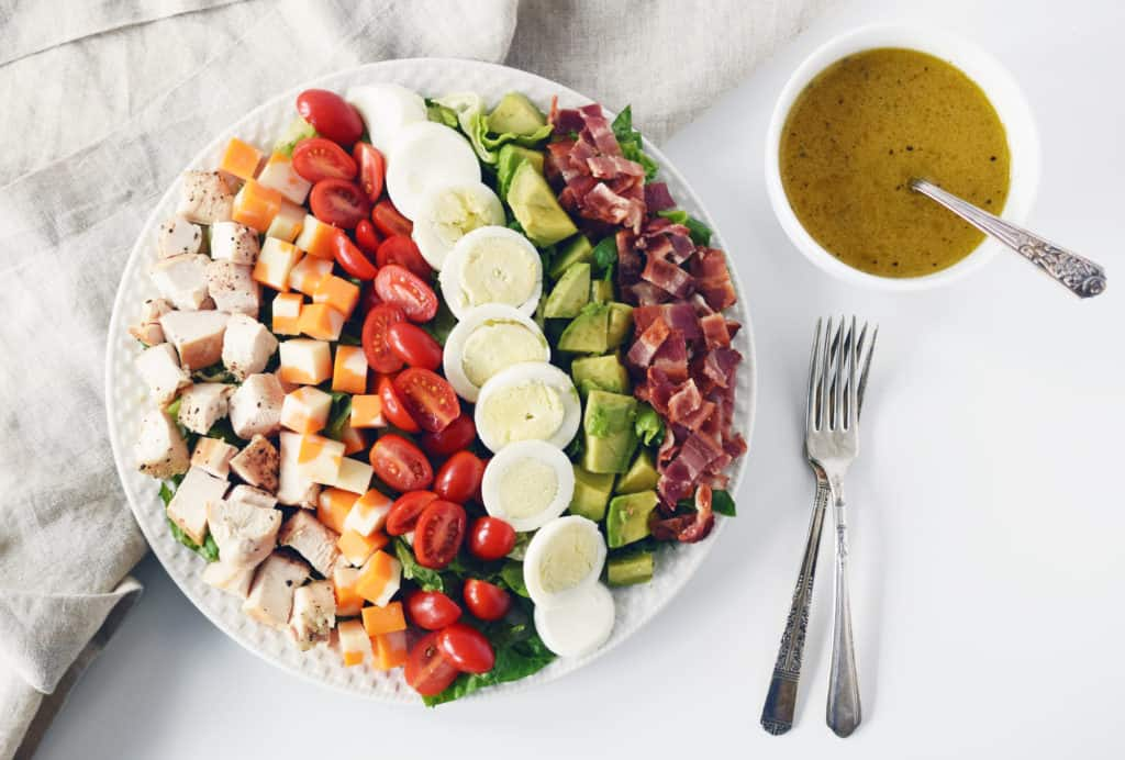 cobb salad on a white plate, two forks bowl of salad dressing with spoon beside it