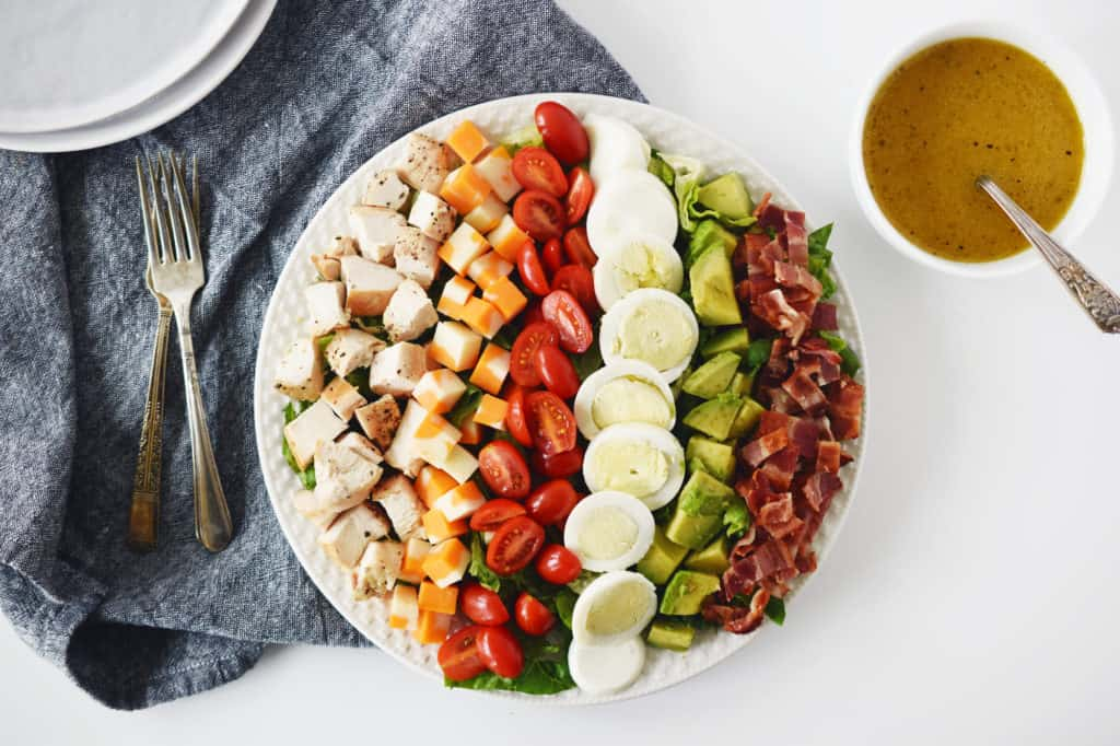 cobb salad on white plate with forks, dark napkin and white bowl of salad dressing beside the plate