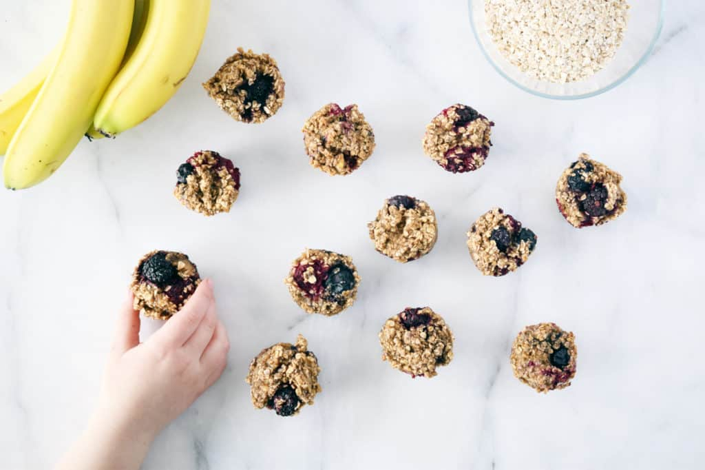 oat berry mini muffins on counter with toddler hand grabbing one. bananas in top corner.