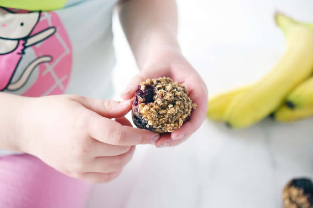 toddler hands holding oat berry muffins
