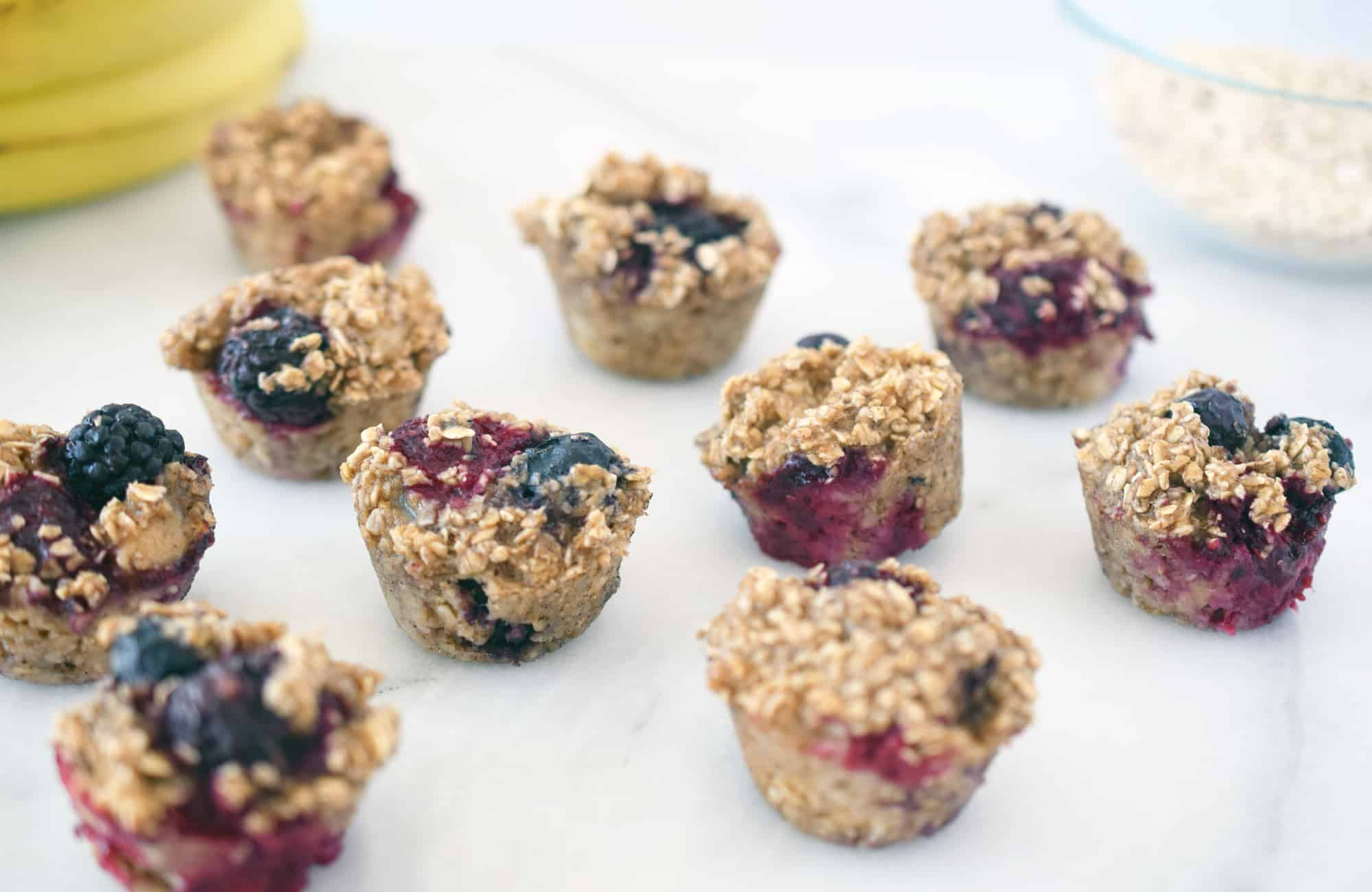 oat berry mini muffins on a white counter with bananas and bowl of rolled oats in the background