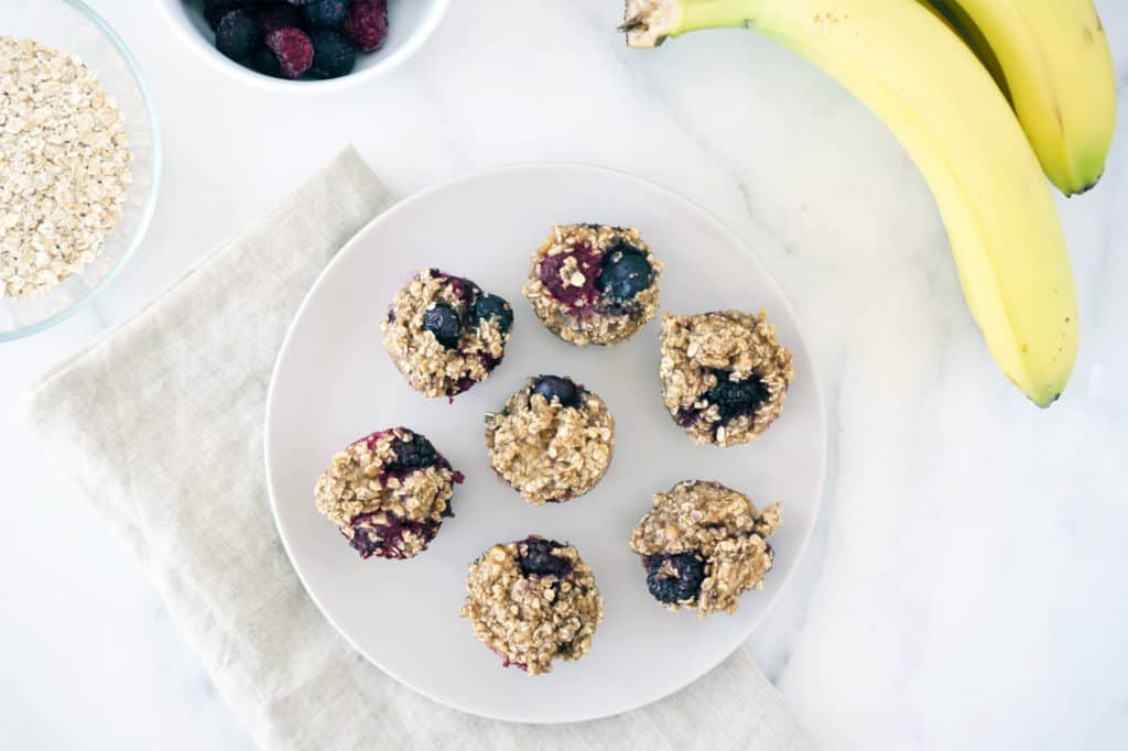mini muffins on a grey plate with beige napkin. Bananas and oats in top corner.