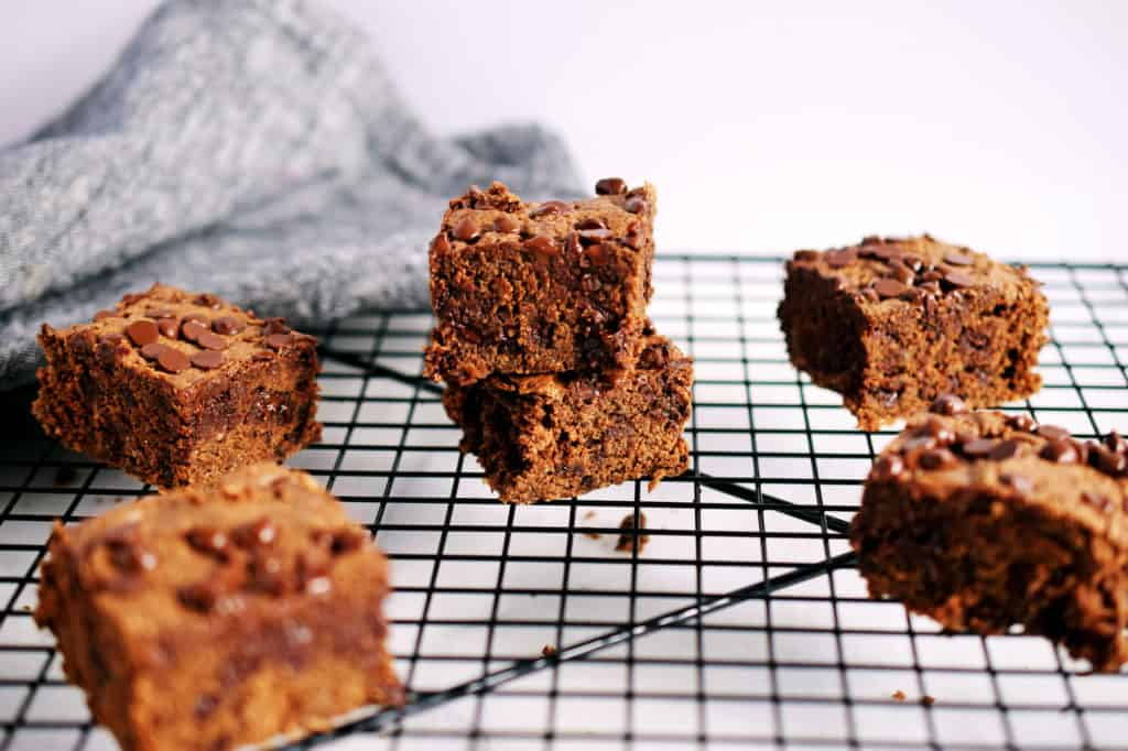 nut butter oat brownies in squares stacked on a black cookie rack with grey napkin in background