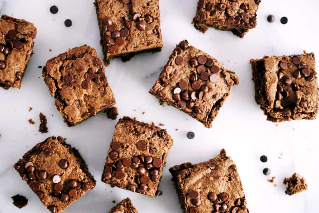 nut butter oat brownies in squares spread out on white marble counter