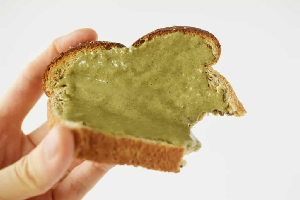 hand holding sunflower seed butter on toast with bite taken out of it