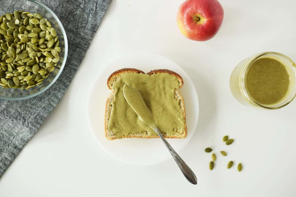 pumpkin seed butter spread on toast with knife. Apple and pumpkin seeds surround it on white counter.