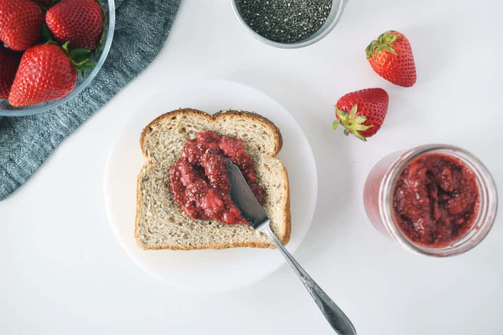 jam spread on toast. Fresh strawberries and mason jar with jam are surrounding it.