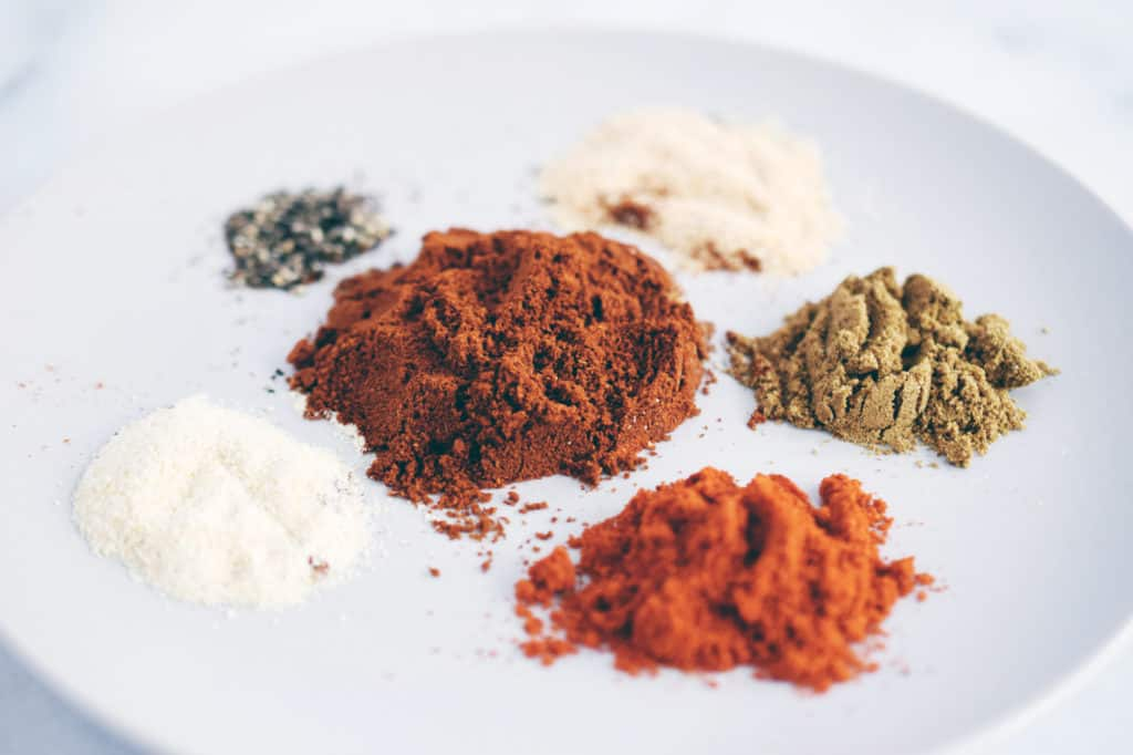 white, brown and red spices all separated on a grey plate