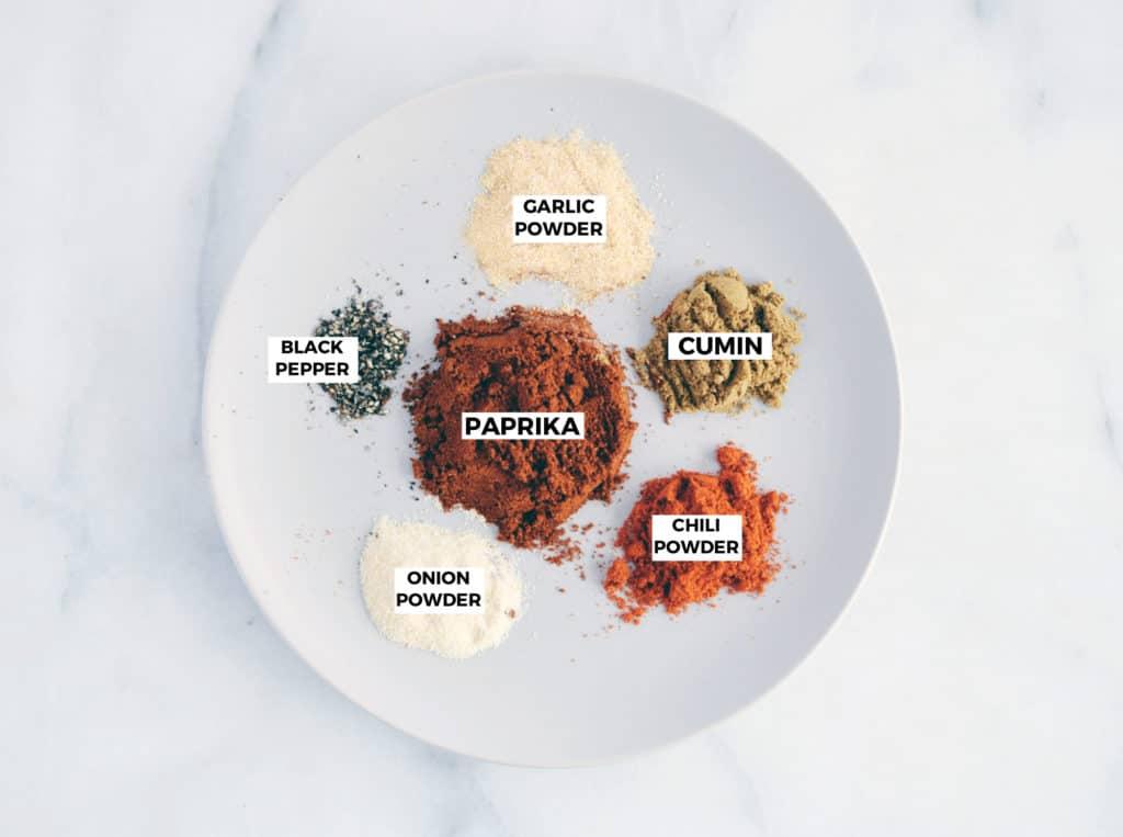 garlic powder, cumin, paprika, black pepper, onion powder, and chili powder on a grey plate.
