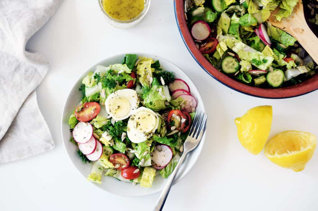 garden salad on a white plate with fork, lemon peels on the side and bowl of garden salad in top right